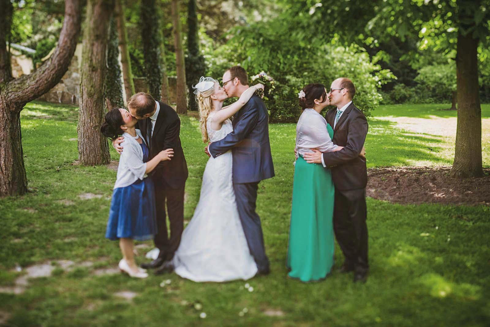 Brautpaar kuesst sich auf Gruppenfoto vom Hochzeitsfotograf Copyright by Hochzeitsfotograf www.berliner-hochzeitsfotografie.de