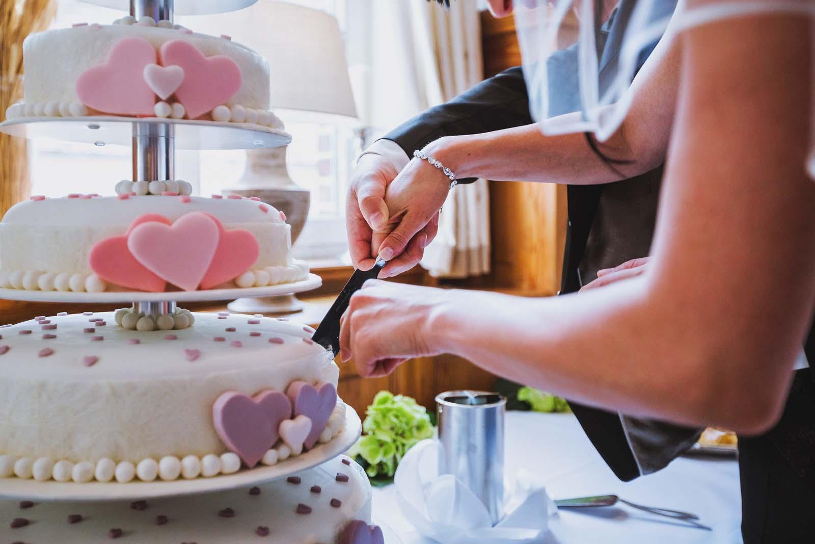 Anschnitt der Hochzeitstorte auf einem Foto mit Details vom Fotograf Copyright by Hochzeitsfotograf www.berliner-hochzeitsfotografie.de
