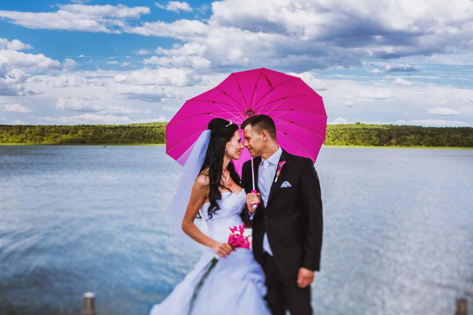 Hochzeitsportrait zeigt Brautpaar mit Schirm in Pink Copyright by Hochzeitsfotograf www.berliner-hochzeitsfotografie.de