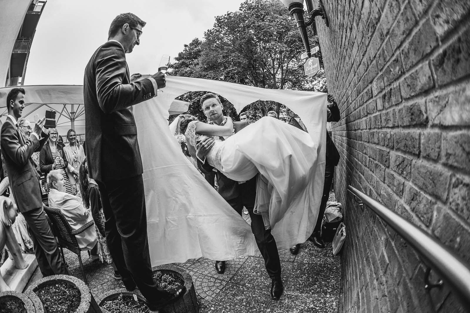 Foto zeigt den Hochzeitsbrauch des zerschneidens eines Bettlakens mit Herz Copyright by Hochzeitsfotograf www.berliner-hochzeitsfotografie.de