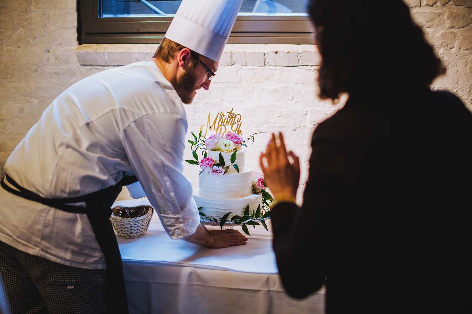 Koch bringt Hochzeitstorte Details einer Hochzeit Copyright by Hochzeitsfotograf www.berliner-hochzeitsfotografie.de