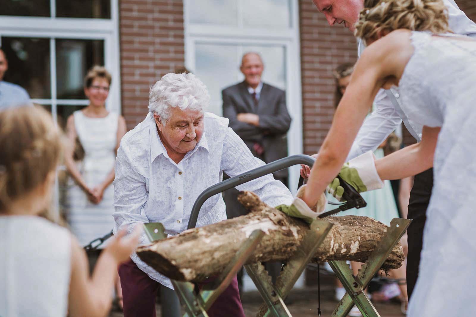 Hochzeitsreportage mit einer Oma beim Baumstammsaegen Copyright by Hochzeitsfotograf www.berliner-hochzeitsfotografie.de